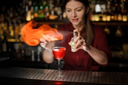 Young female bartender sprinkling a cocktail glass with tasty Aperol syringe cocktail with a peated whisky and making a smoky note