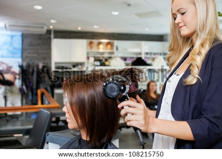 Young female beautician giving a new hair style to woman at parlor