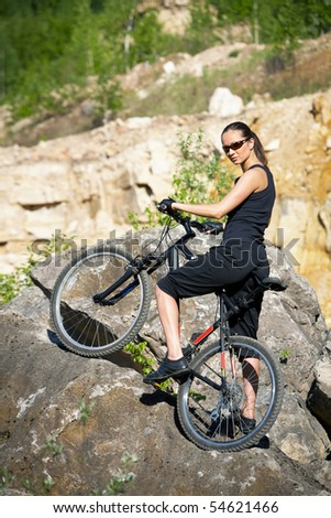 young female biker athlete resting up in a mountains