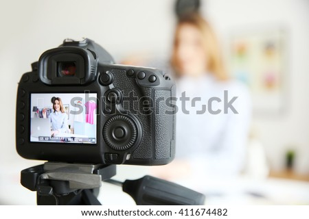 Young female blogger on camera screen