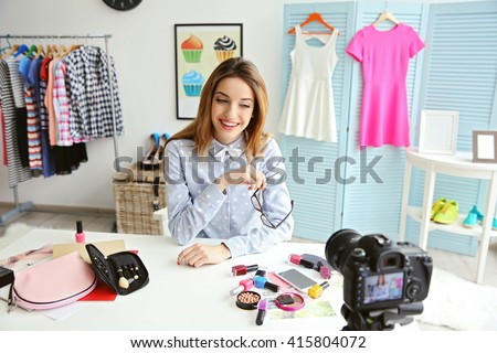 Young female blogger with makeup cosmetics recording video at home
