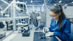 Young Female Blue and White Work Coat is Using Plier to Assemble Printed Circuit Board for Smartphone. Electronics Factory Workers in a High Tech Factory Facility.