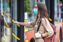 Young female boarding a city bus. Virus pandemic and pollution concept. Woman getting on the bus with protective medical mask and gloves against coronavirus, Covid-2019