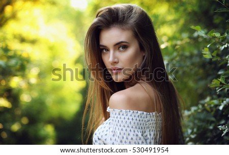 Young female brunette walking in the park