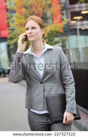 Young female business leader walks with a leather folder in hand and talks by phone.