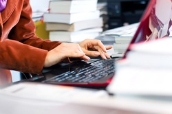 Young female, business woman typing on laptop keyboard surrounded by books and files. Business environment wallpaper