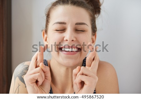 Young female Caucasian student keeping her fingers crossed and eyes closed to make a desired wish. Charming white smile, positive heartwarming look of girl sincerely believing in her victory. #495867520