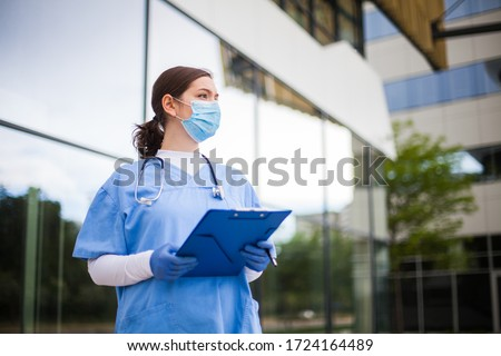 Young female caucasian UK doctor looking in distance with fear worry anxiety  uncertainty in eyes,wearing uniform  face mask,hope  faith  overcoming global Coronavirus COVID-19 pandemic crisis