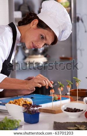 Young female chef adding the finishing touch to her amuse