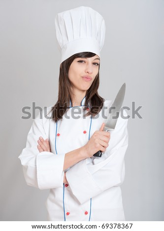 Young female chef holding a carving knife with a funny expression