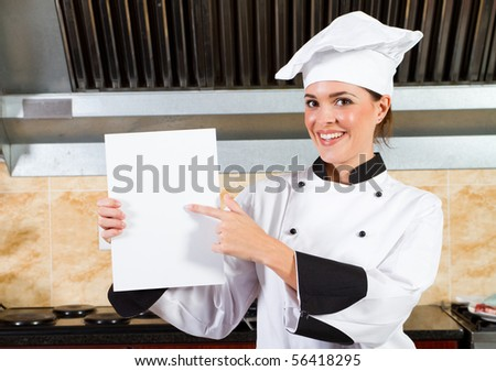 young female chef holding a white board or menu in kitchen