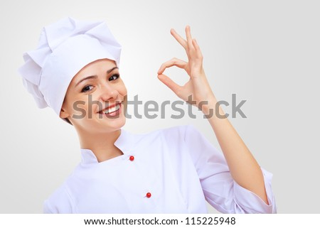 Young female chef in red apron against grey background