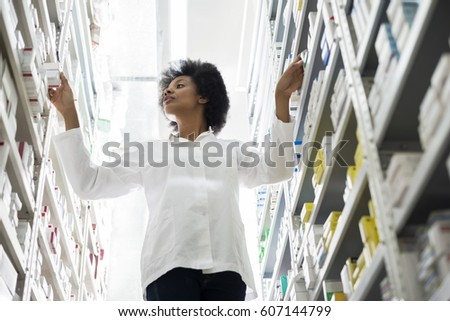 Young Female Chemist Arranging Stock In Shelves At Pharmacy
