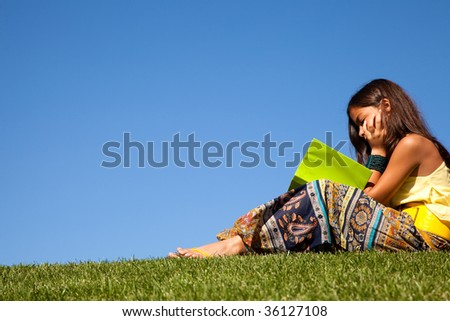 young female child at the park reading a book