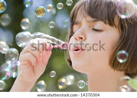 young female child blowing a stream of bubbles into the air