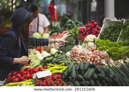 Young Female Choosing Vegetables At Market Place