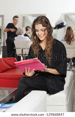 Young female client using digital tablet with hairdresser and women in the background in salon