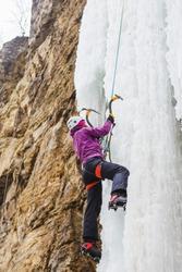 Young female climber climbing frozen waterfall