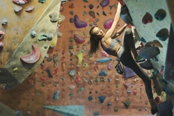 Young female climber Climbing Inside climbing Gym. slim pretty Woman Exercising At Indoor Climbing Gym Wall. Concept of strength, sport, healthy lifestyle.
