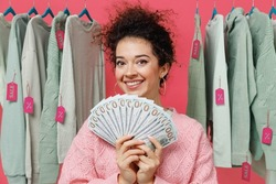 Young female costumer woman 20s wear sweater stand near clothes rack with tag sale in store showroom holding fan of cash money in dollar banknotes isolated on plain pink background studio portrait.