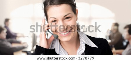Young female customer service representative receives calls on a headset while colleagues are working on computers in the background.