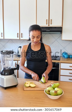 young female cutting fruits in kitchen preparing a smoothie