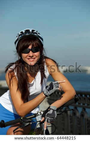 Young female cyclist in the helmet on the city river-quay pointing aside