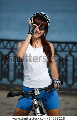 Young female cyclist in the helmet on the city river-quay showing ok sign