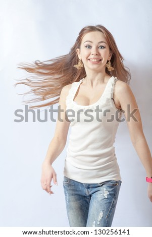 Young female dancing, fluttering on the wind hair, over white background