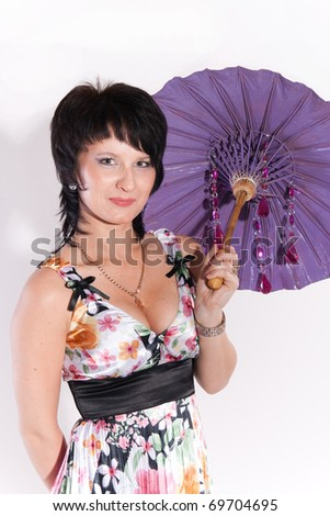 Young female dark-haired model wearing colored dress with printed flowers posing with Japanese-style purple umbrella in studio, on white