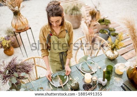 Young female decorator or florist putting herbs on the table, decorating lunch place in natural Boho style in green tones outdoors Stock photo ©