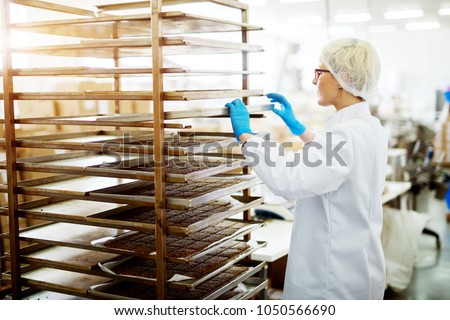 Young female dedicated bakery worker in sterile cloths placing tinplate with hot freshly baked cookies on a rack to cool off.