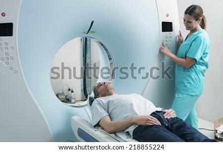 Young female doctor examining man in 40s with CT scanner. Computerised tomography.