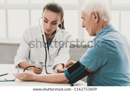Young Female Doctor Examining Senior Patient. Young Woman Doctor Wearing White Coat Examining Senior Man Sitting at Desk in Hospital. Doctor Measuring Blood Preasure Healthcare Medicine Concept