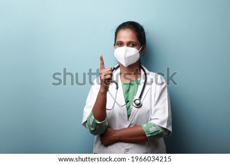Young female doctor of Indian origin wearing face mask shows her index finger Сток-фото ©