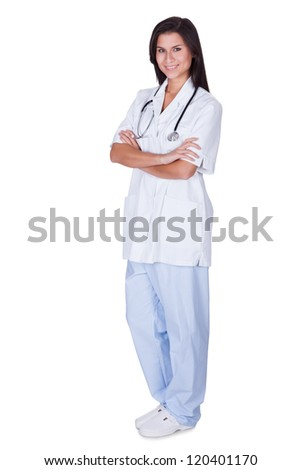 Young female doctor or nurse standing full length with a stethoscope around her neck and arms folded isolated on white