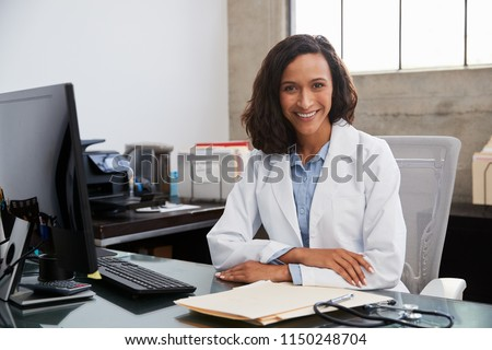 Young female doctor sitting at desk in an office, portrait