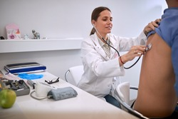Young female doctor with stetoscope listening male patient