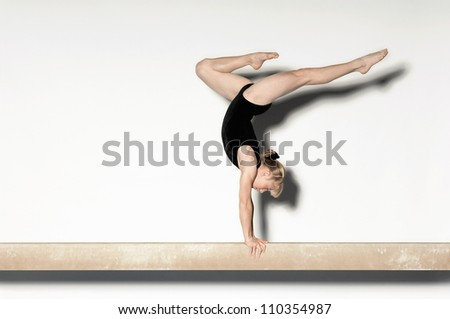 Young female doing a handstand on balance beam