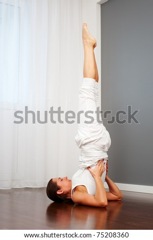 young female doing yoga exercise on floor