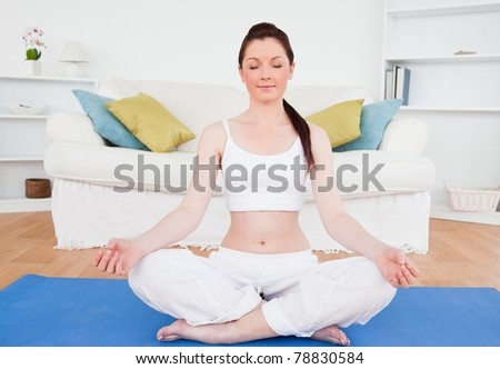 Young female doing yoga on a gym carpet in the living room