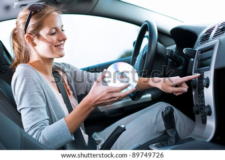 Young female driver playing music in the car (changing CDs)