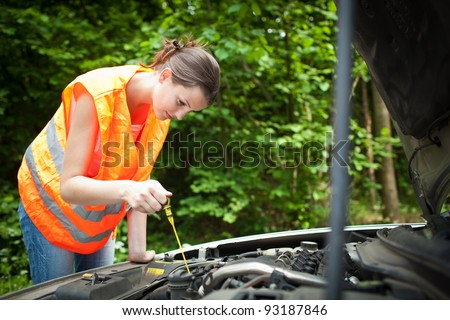 Young female driver wearing a high visibility vest, bending over the engine of her broken down car