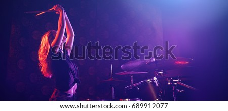 Young female drummer playing drum kit on illuminated stage in nightclub #689912077