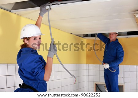 Young female electrician with mentor