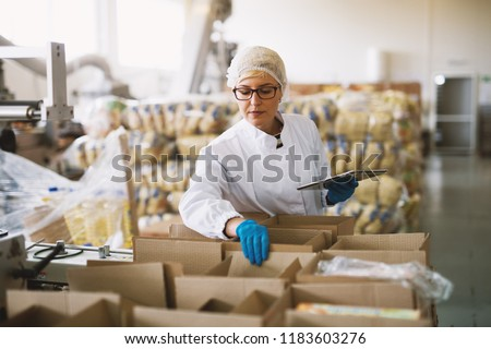 Young female employee in sterile clothes is checking packages ready to be delivered.