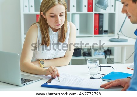 Young female employee of the staffing agency helps fill out the form to the male job seeker. Business, office, law and legal concept