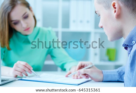 Young female employee of the staffing agency helps fill out the form to the male job seeker. Business, office, law and legal concept.