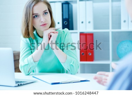 Young female employee of the staffing agency listening attentively the male job seeker. Business, office, law and legal concept.