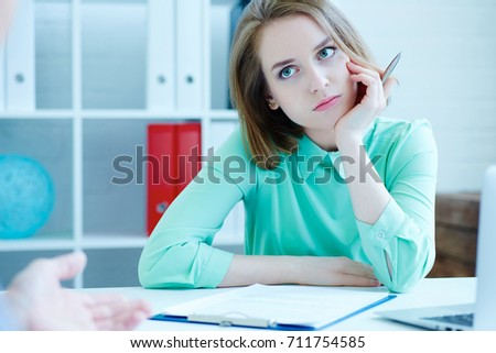 Young female employee of the staffing agency listening bored the male job seeker.